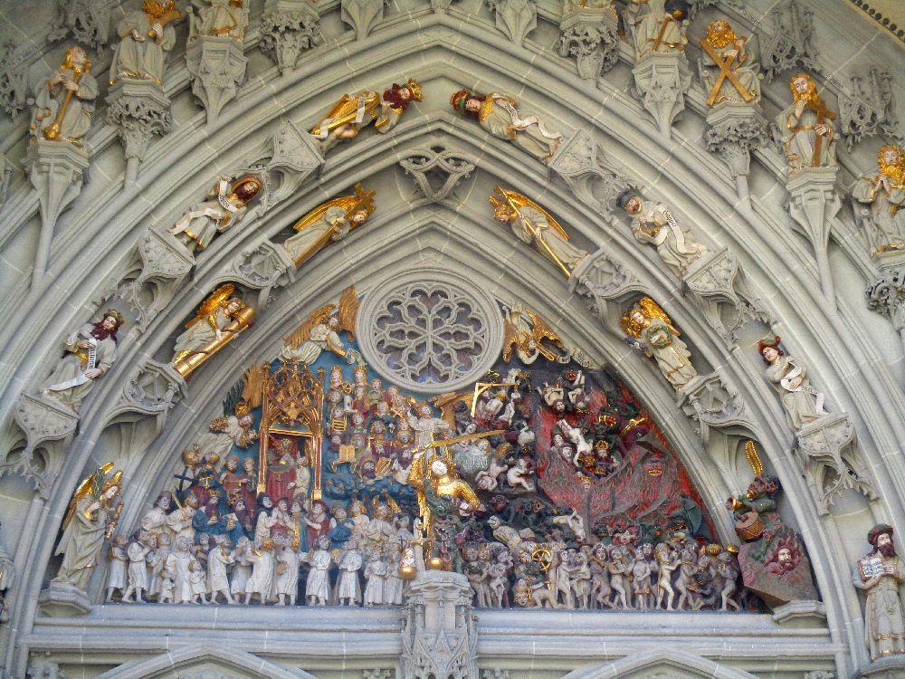 Die Bunten Figuren des Berner Münsterportales. Ein Bild zeigt Justizia im Vordergrund, die Hölle ist auf der rechts seite und der Himmel auf der linken Seite des Reliefs dargestellt.