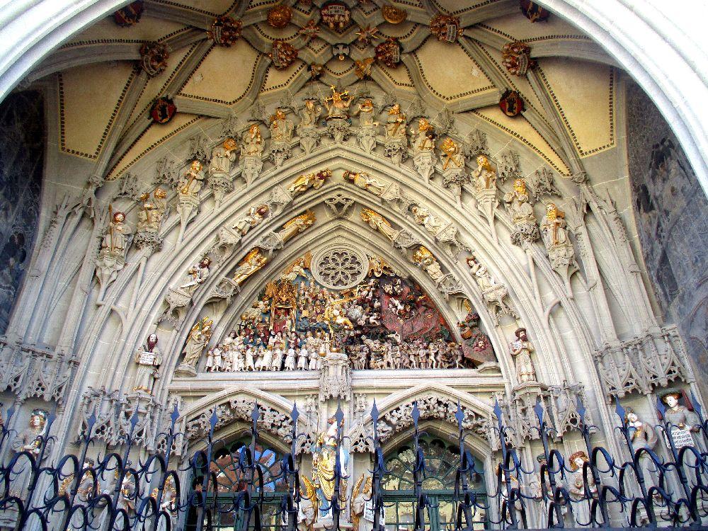 Das Berner Münsterportal aus einer Froschperspektive. Zu sehen ist der vorgelagerte Schutzzaun, dahinter liegen Bunte Figuren, viele sind mit gold bemalt.