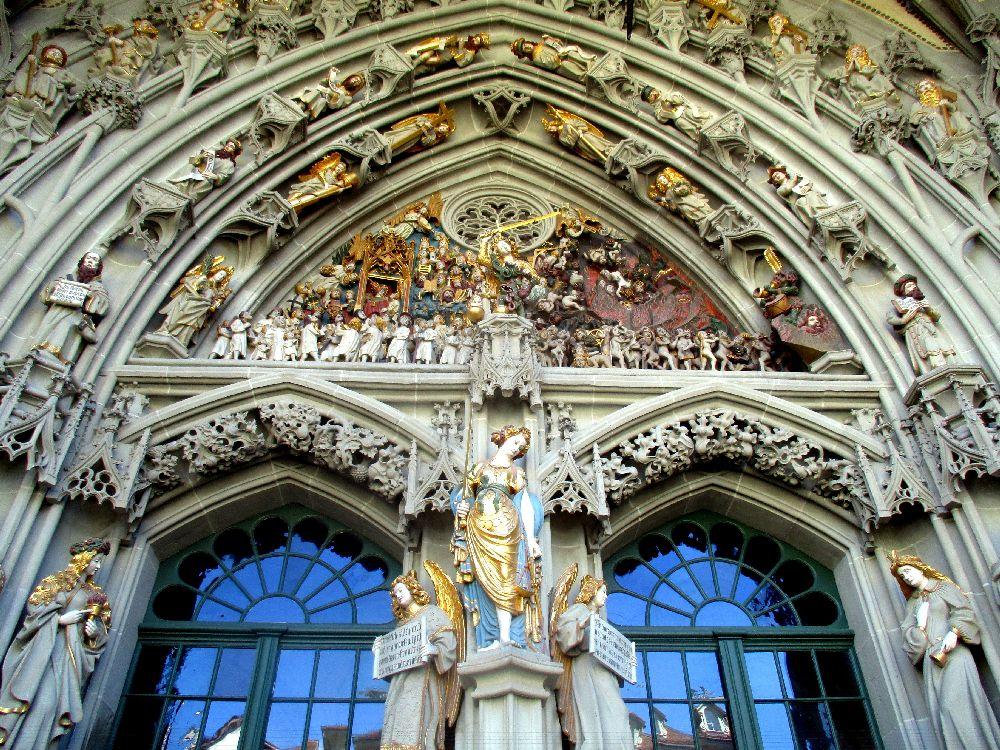 Das Berner Münsterportal aus der Froschperspektive. Im Zentrum steht die Justitia in blau goldemem Gewand.
