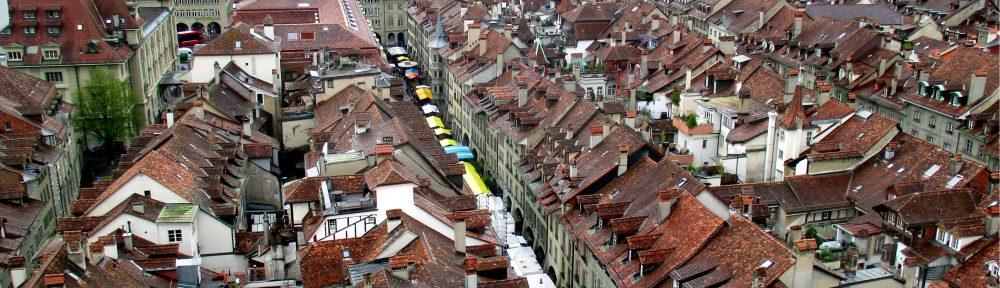 Bern von Oben. In einer langen Straße ist in Markt zu sehen. Er verschwindet in einem roten Dächermeer.