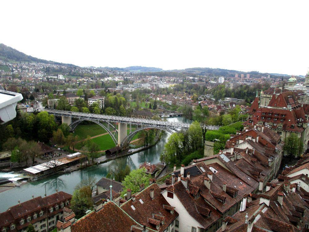 Das Berner Dächermeer vom Münsterturm aus gesehen. Die Aussicht fällt in richtug Aare. der grüne Fluss wird von einer Hohen Metallbrücke überquert.