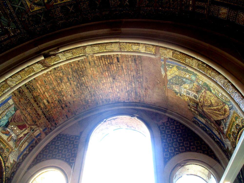Ein Gemauerter Backsteinbogen vor einem Bogenfenster. Reste von Mosaiken, die einmal an dem Backsteinbau angebracht waren sind zu erkennen.