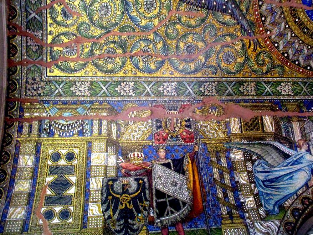Ein Mosaik auf der Berliner Gedächtniskirche. Es handelt sich um ein beschädigtes Wandbild das ein Wappen zeigt, und einen Mann mit ausgebreiteten Armen.
