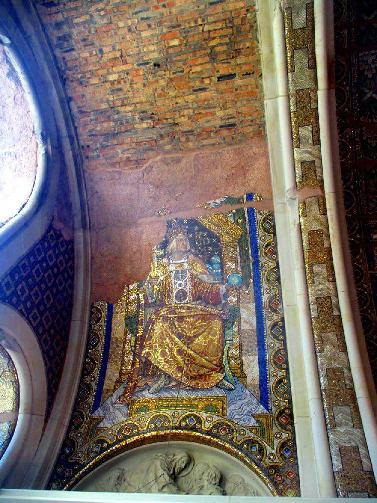 Mosaikrest an einer Backsteinwand in der Kaiser Wilhelm Gedächtnisskirche. Das Mosaik zeigt einen Herrscher auf deinem Thron. Der Herrscher trägt ein goldenes Gewand und eine goldene Krone.