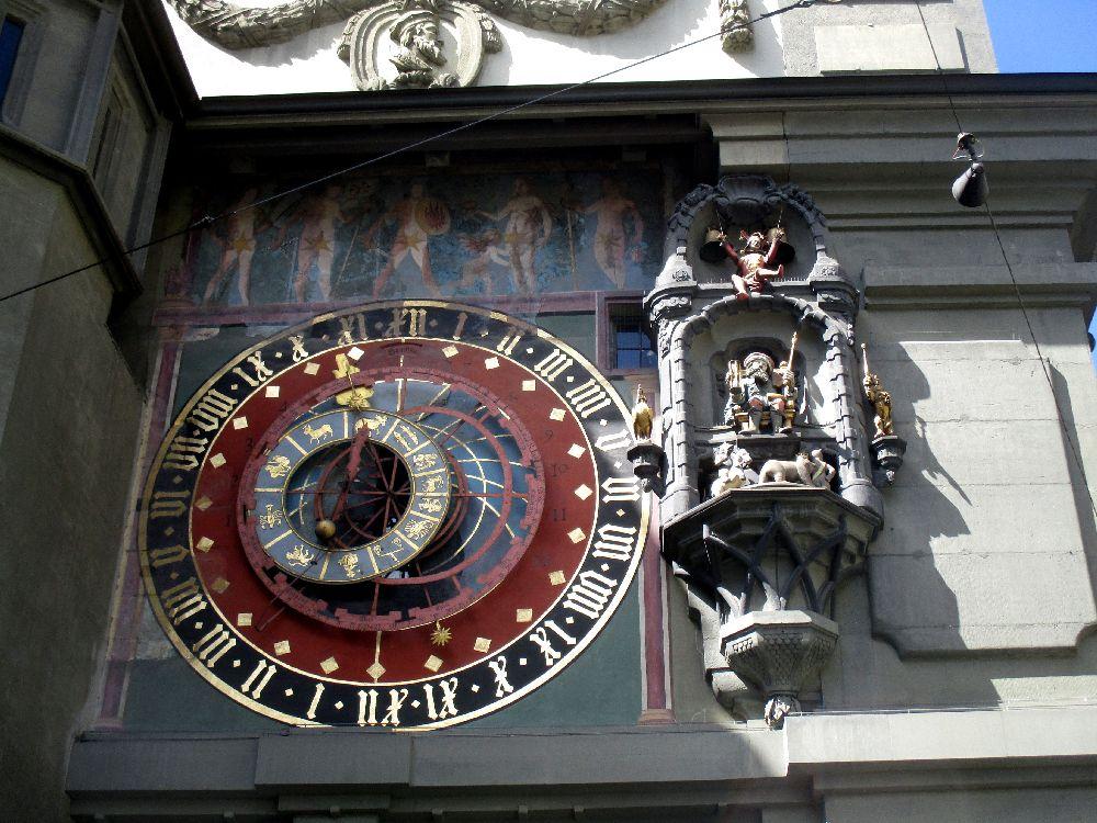 Detailaufnahme von der Uhr an der Zytglogge in Bern. Links Befindet sich eine Uhranzeige, die nicht nur die Uhrzeit, sondern auch das Aktuelle Sternzeichen anzeigt. Rechts davon befindet sich eine Renaisancefigur die sich zur vollen Stunde dreht.