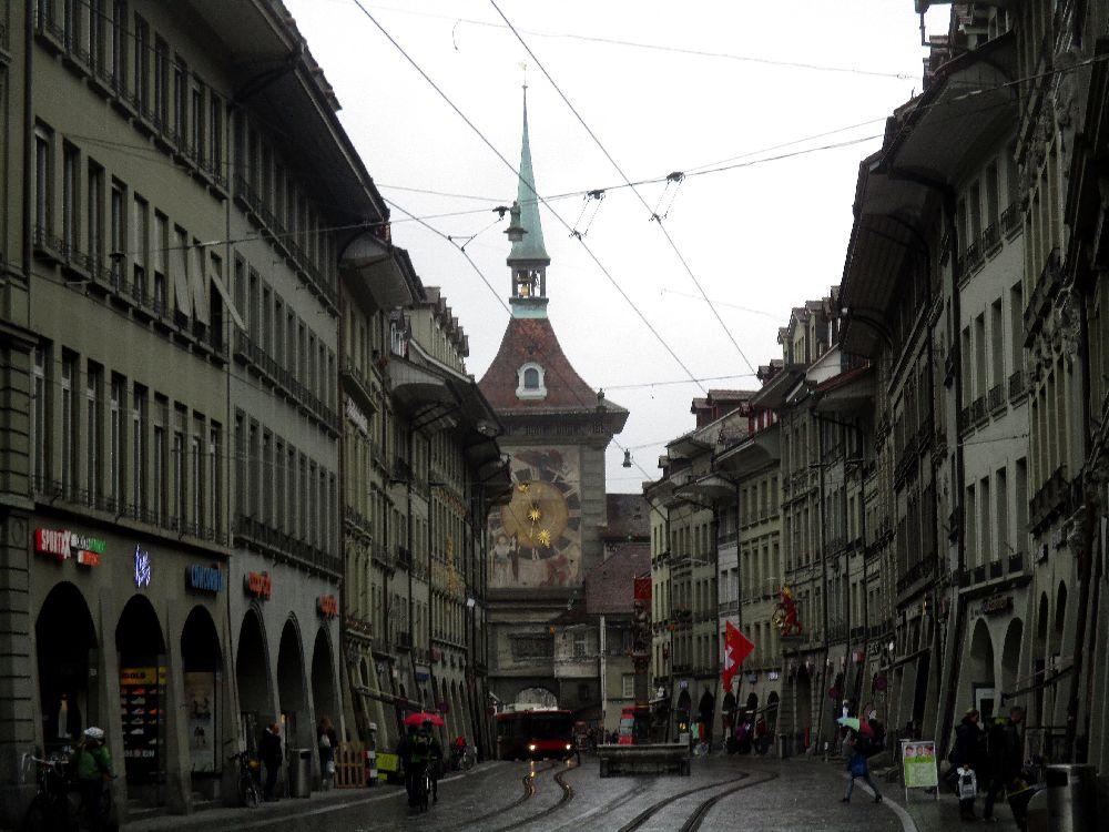 Der Stadtturm von Bern mit der Zytglogge von weitem. Er ist am einde einer Gebogenen mittelalterlichen strasse zu sehen, und verschwindet ein wenig hinter einer Kurve.
