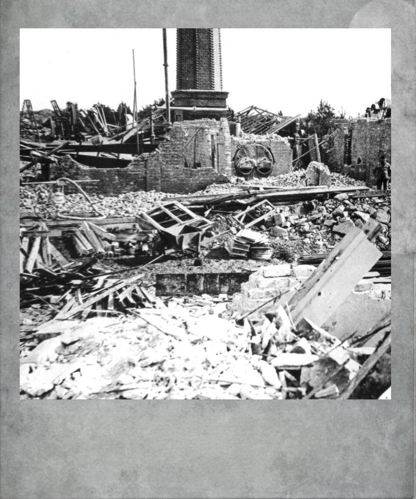 Eine Grafik eines scheinbaren Polaroidbildes. Das Bild zeigt die Reste einer explodierten Fabrik. Überall liegen trümmer, nur ein Schornstein steht noch dort.