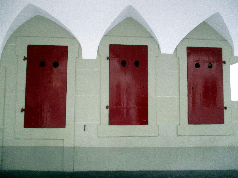 Die alte Post in Bern. Sie hat rote Schaltertüren nach Aussen, in eine Akkarde. Diese sind geschlossen. Es handelt sich um rote Holzfenster.