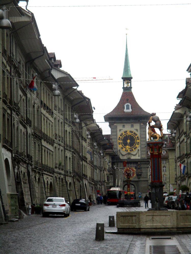 Die berner Zytglogge im Hintergrund und ein Brunnen mit einer Brunnenfigur im Vordergrund. Links und rechts sind Häuser mit Laubengängen zu sehen. Die Brunnen steht inmitten einer gepflasterten Strasse.
