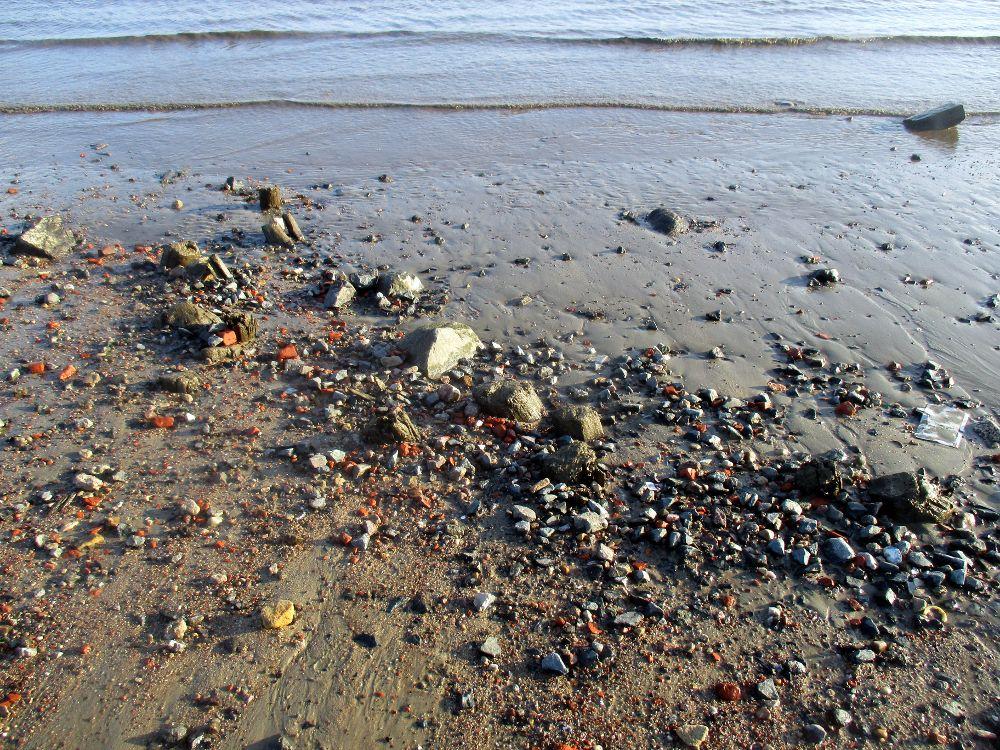 Bruchstein und anderes Strandgut am Elbstrand in Wedel.