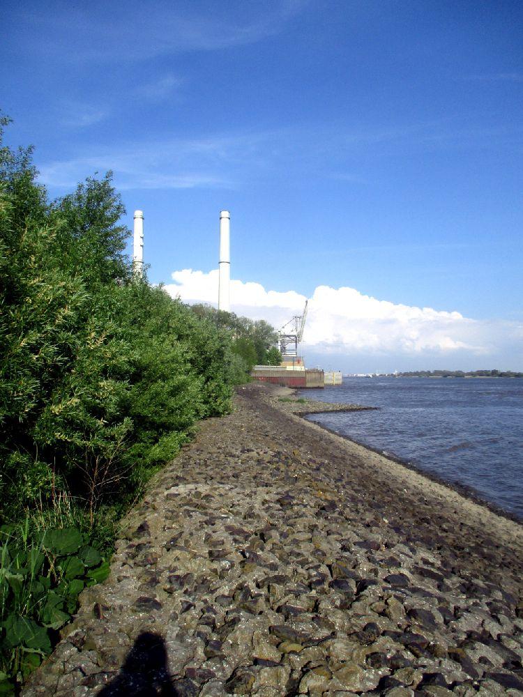 Das Wedeler Kraftwerk am Elbstrand mit seinen hohen Schornsteinen. Im Fordergrund ist die Uferbefestigung zu sehen.