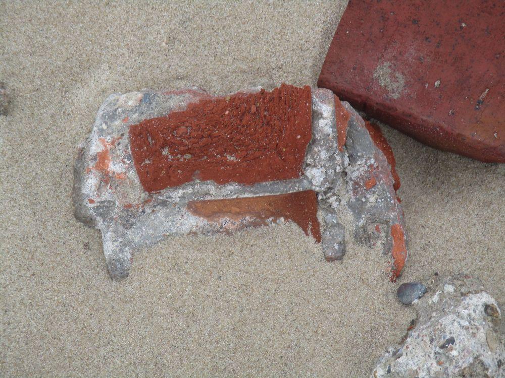 Ein Ziegelmauerrest liegt im Strandsand.