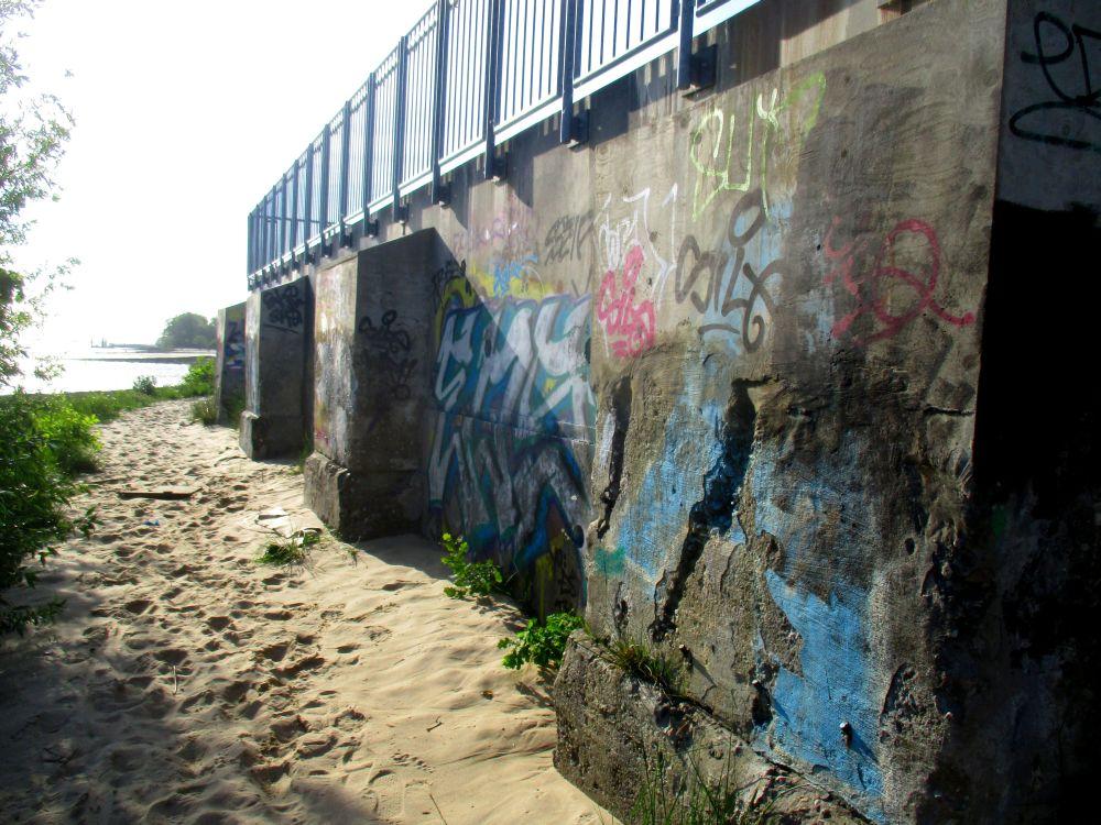 Ein Angespraytes Gebäude im Strandsand. Es handelt sich um den zubetonierten Eingang zum Zuckerspeicher.