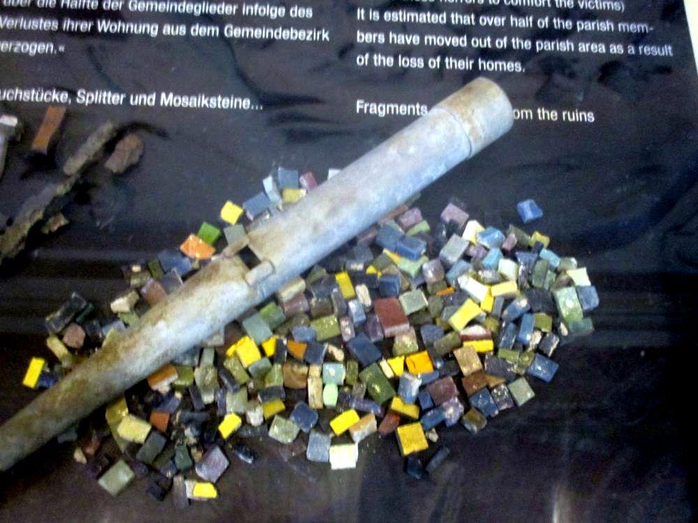 Mosaiksteine und eine kaputte Orgelpfeife in einer Vitrine. Es handelt sich um Reste die nach dem zweiten Weltkrieg in der zerstörrten Region der Kaiser Wilhelm Gedächtniskirche gefunden wurden.