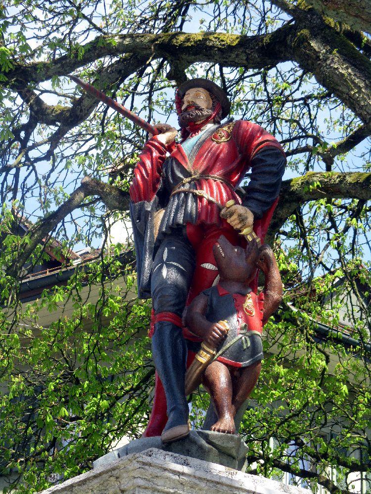 Berner Brunnenfigur eines Mannes mit einem Braunen Bart. Es handelt sich um einen Wanderer Mit wanderstock und Bündel. Er trägt blau-rote Kleidung, und ein Bärenkind begleitet ihn.