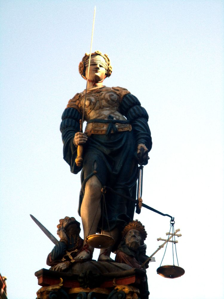 Die Brunnenfigur des Justiziabrunnen. Es handelt sich um eine bemalte Figur aus dem 16. Jahrhundert. Die Justitia hat einen goldenen Pazer an, über einem blauen Gewand. In der einen Hand hält sie ein Schwert, in der anderen eine Waage. Die Augen sind ihr verbunden.