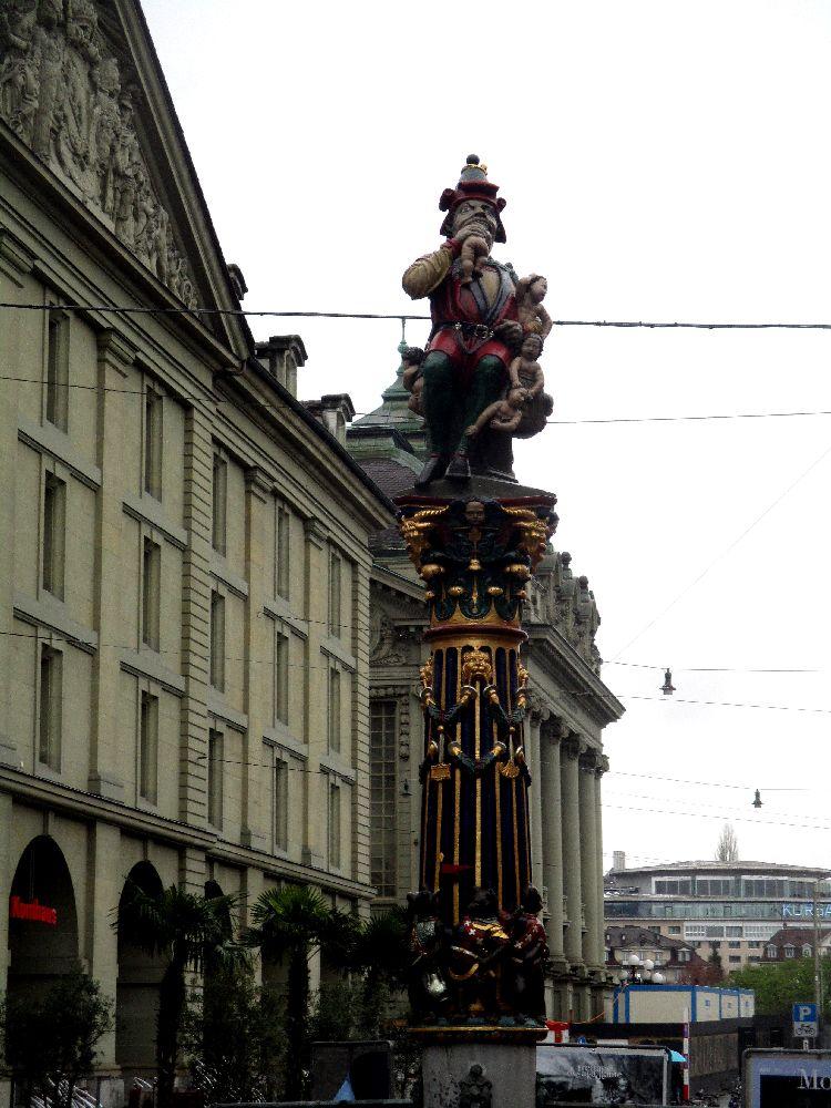 Der Kindlifresserbrunen in der Berner Altstadt. Der Brunnen hat eine Figur, die auf einer Säule staht. Ein Mann in rosa oder pinker Kleidung, mit einem Spitzhut auf dem Kopf. Der Mann beist einem Baby den Kopf ab.