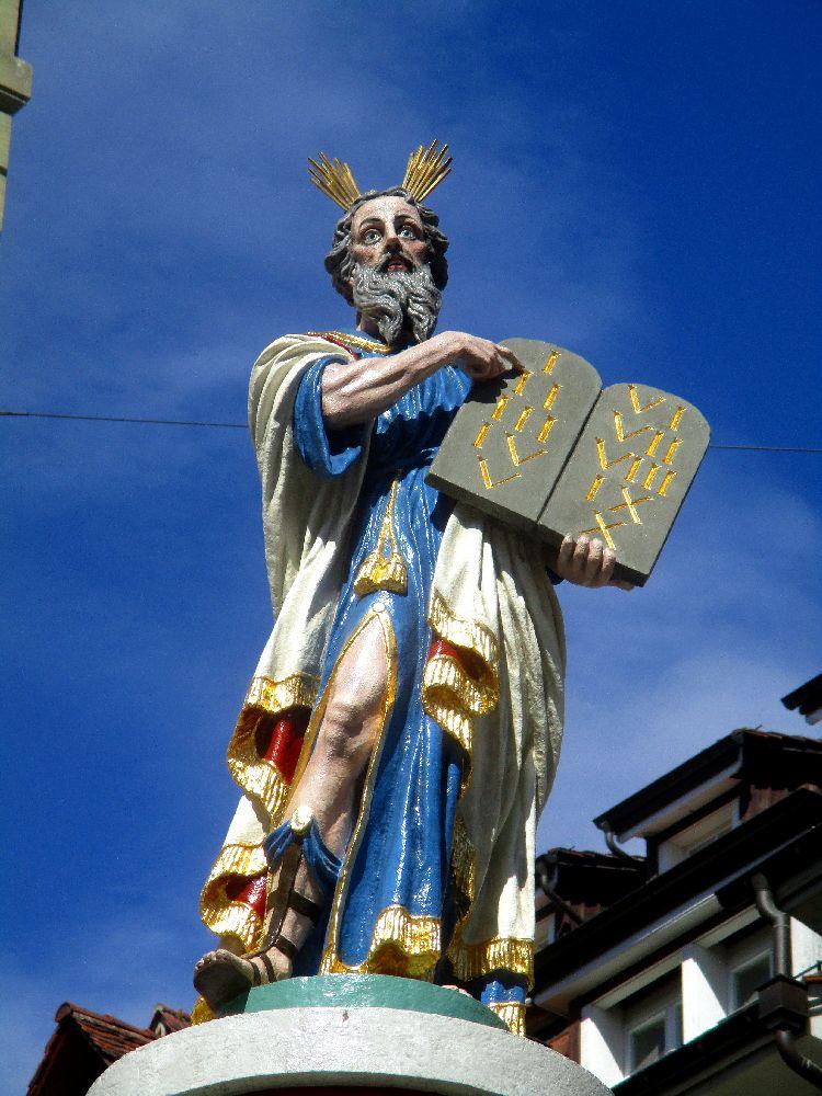 Der Moesesbrunnen von Bern. Er ist mit einer figur versehen die Moses mit den Tafeln der 10 Gebote zeigt. Moses deutet auf das erste Gebot. Er trägt ein blaues Kleid, und eine weiß-golden-purpurne Stola.