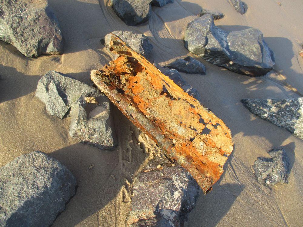 Ein Schrotteil, vielleicht eine alte Regenrinne liegt im Sand des Elbstrandes. Der Metallrest ist sehr verrostet und leuschtet orange in der Sonne.