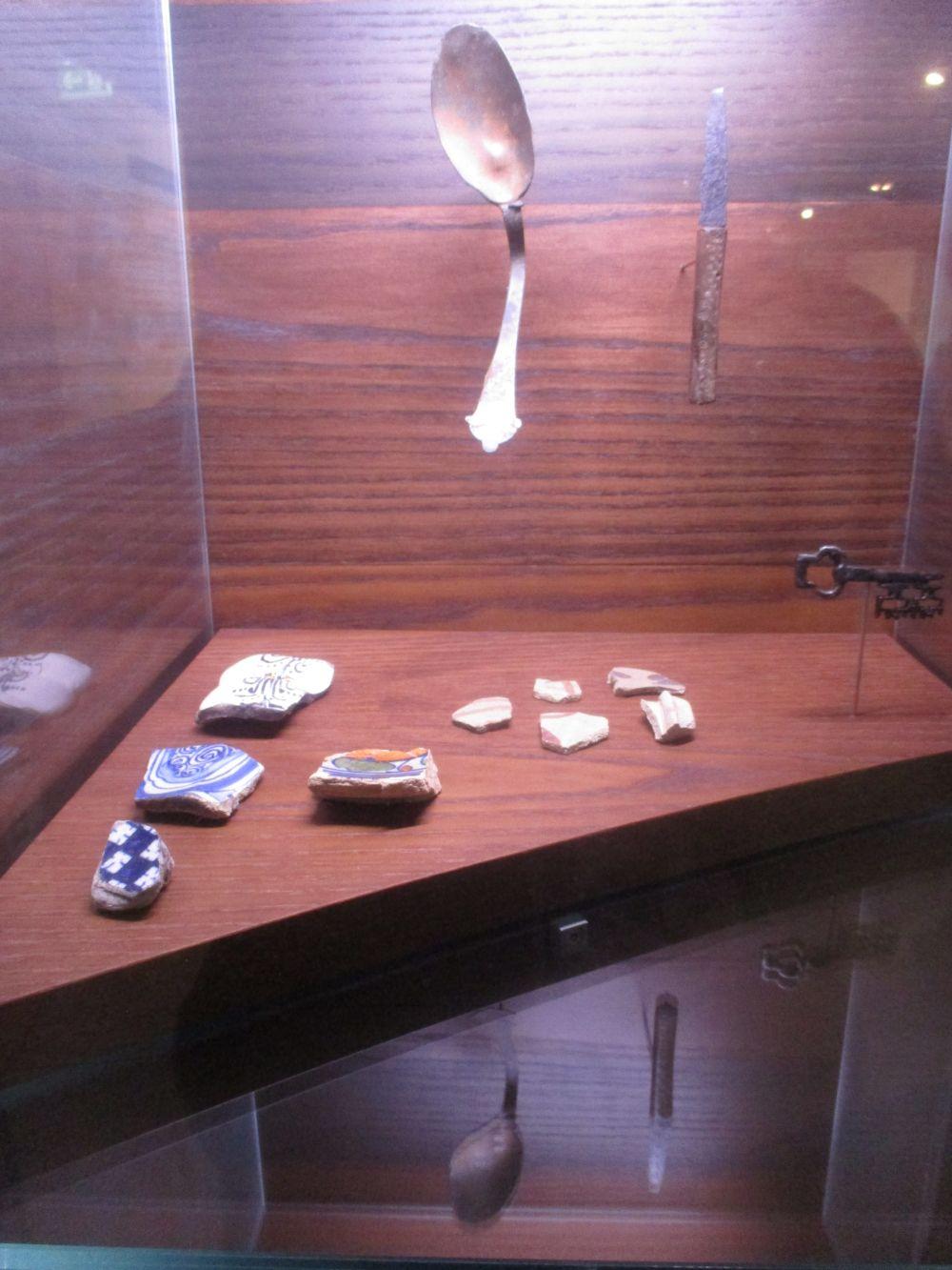 Funde aus dem Hafenbecken in Stade durcheinander in einer Virtrine plaziert. Ein Löffel Bruchstücke von Keramik, ein Schlüssel und Reste von Fliesen.