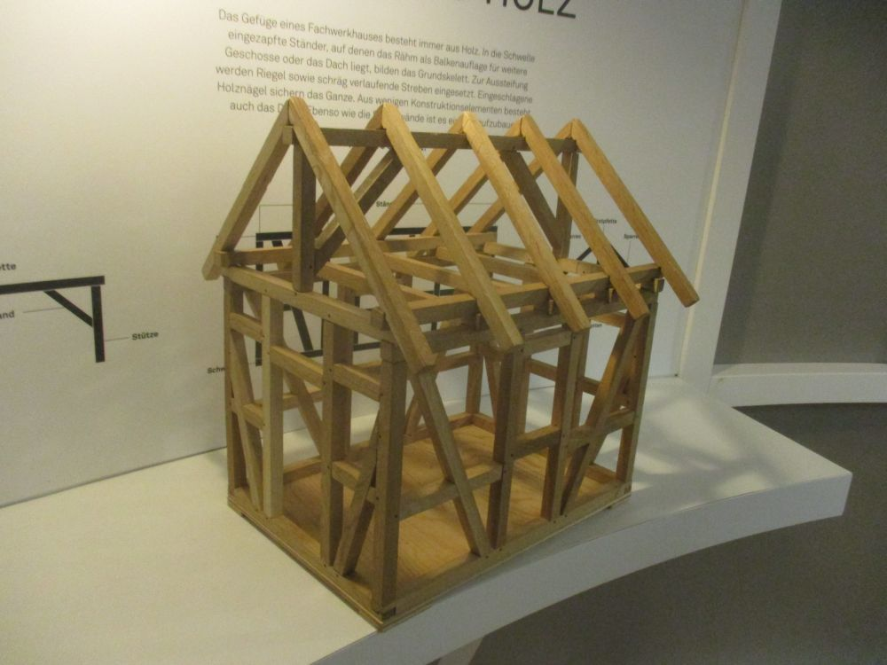 Die Miniatur einer Grundkonstrucktes von einem Fachwerkhaus. Es handelt sich um ein Kinderspiel bei dem man die Holzbalken selber zusammen setzt bis ein Fachwerkhaus endsteht.