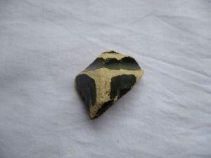 Ofenkachelbruchstück. Das Bruchstück bestht aus Ton, ist sehr vergangen aber es sind reste dunkelgrüner Glasur zu erkennen.