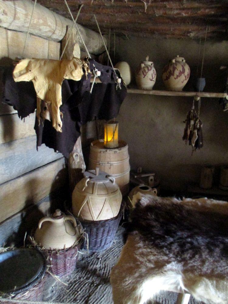 Die Innenausstattung eines Wikingerhauses in Haithabu. Es handelt sich um eineige Reliefbandamaphoren, und gelagerte Dinge wie beispielsweise Lederstücke die zum Tockenen aufgehangen sind. Auf einem Regal stehen einige Gefäße aus Pingsdorfer Keramik. Auch einige Körbe sind zu sehen.