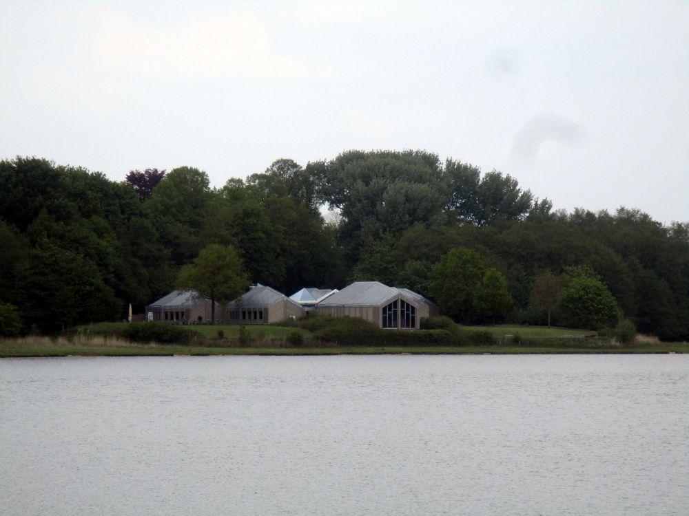 Das Gebäude des Wikigermuseums In Haithabu. Es ist dierekt am Wasser gelegen in einem Wald. Das Museum besteht aus eingeschossiegen Häusern, die aussehen wie silbergraue umgedrehte Schiffe.