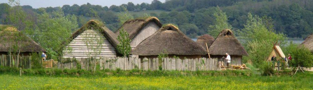 Der rekonstruierte Teil der Wikingerstadt Haithabu von weitem. Einige Holz-Lehm-Häuser sind von weitem auf einer Blumenwiese zu sehen. Sie sind von einer Palisade aus Holz umgeben und mit Schilf gedeckt.