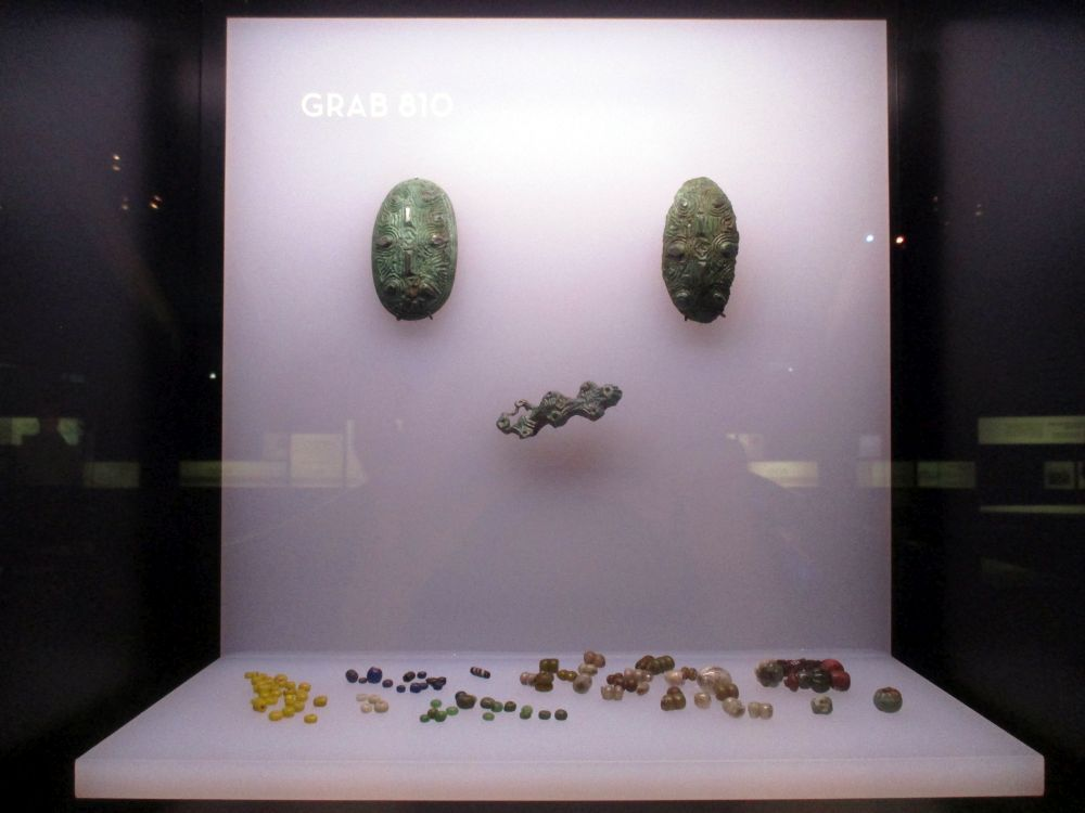 Die Objekte aus dem Grabinventar einer Frau aus Haithabu. Es handelt sich um zwei schallenfiebeln, eine Spange und unzählbar viele Glasperlen einer Perlenkette.