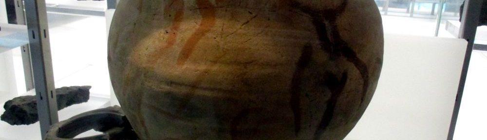 Ein Behälter Pingsdorfer Keramik. Es handelt sich um ein Vorratsgefäß von etwa einem halben Meter höhe. Die Keramik ist terrakottafarben, und mit Rotorangen schlieren verziert, die sich wil über die Oberseite des Tons ziehen.
