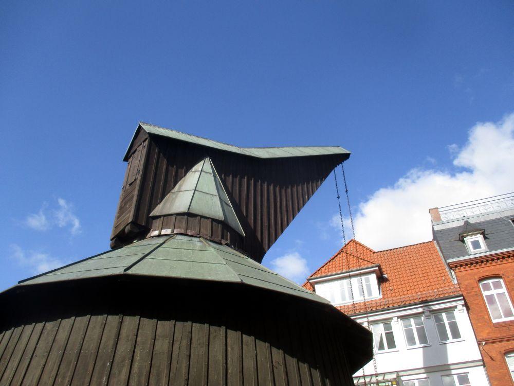 Holzkran mit Dach. Zu sehen ist der obere Teil des Krans, an dem die Halterung für ein Seil zu sehen ist. Die geneue Konsturktion bleibt aber hinter der Holzverkleidung verborgen. Der Kran ist ein Nachbau eines Krans aus dem 13. Jahrhundert. Er steht in der Altstadt von Stade.