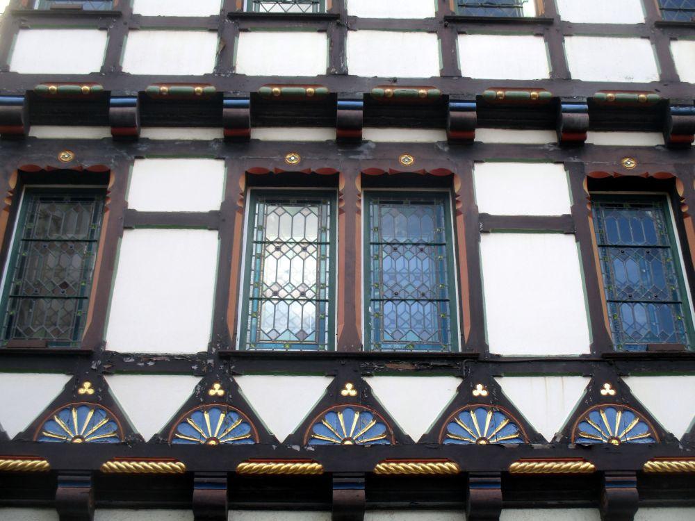 Ausschnitt einer Fassade eines Fachwerkhauses in Stade. Das Haus hat schwarze Balken, und ist mit mit Lehm gebaut, der weiß bemalt ist. Aufändiege Holzintarsien sind in die Baustrucktur eingearbeitet. Sie sind Blau und Gold ausgemalt.