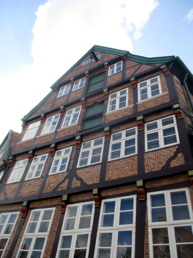 Das Kunsthaus Wasser West. Ein Fachwerkhaus, mit Ziegelmauer aus rotem Backstein. Das Hlz des Fachwerkes ist Braum bemalt. Einige Intarsien sind in Rot und Gelb gehalten. Das Gebäude ist bis zum Giebel hin ausgebaut, und hat von daher vier Stockwerke. in Zwei obenliegenden Stockwerken befinden sich Grün gestrichene Türen, die Früher als Speihereingang dienten Pber ihnen ist die Halterung für einen Flaschenzug angebracht.