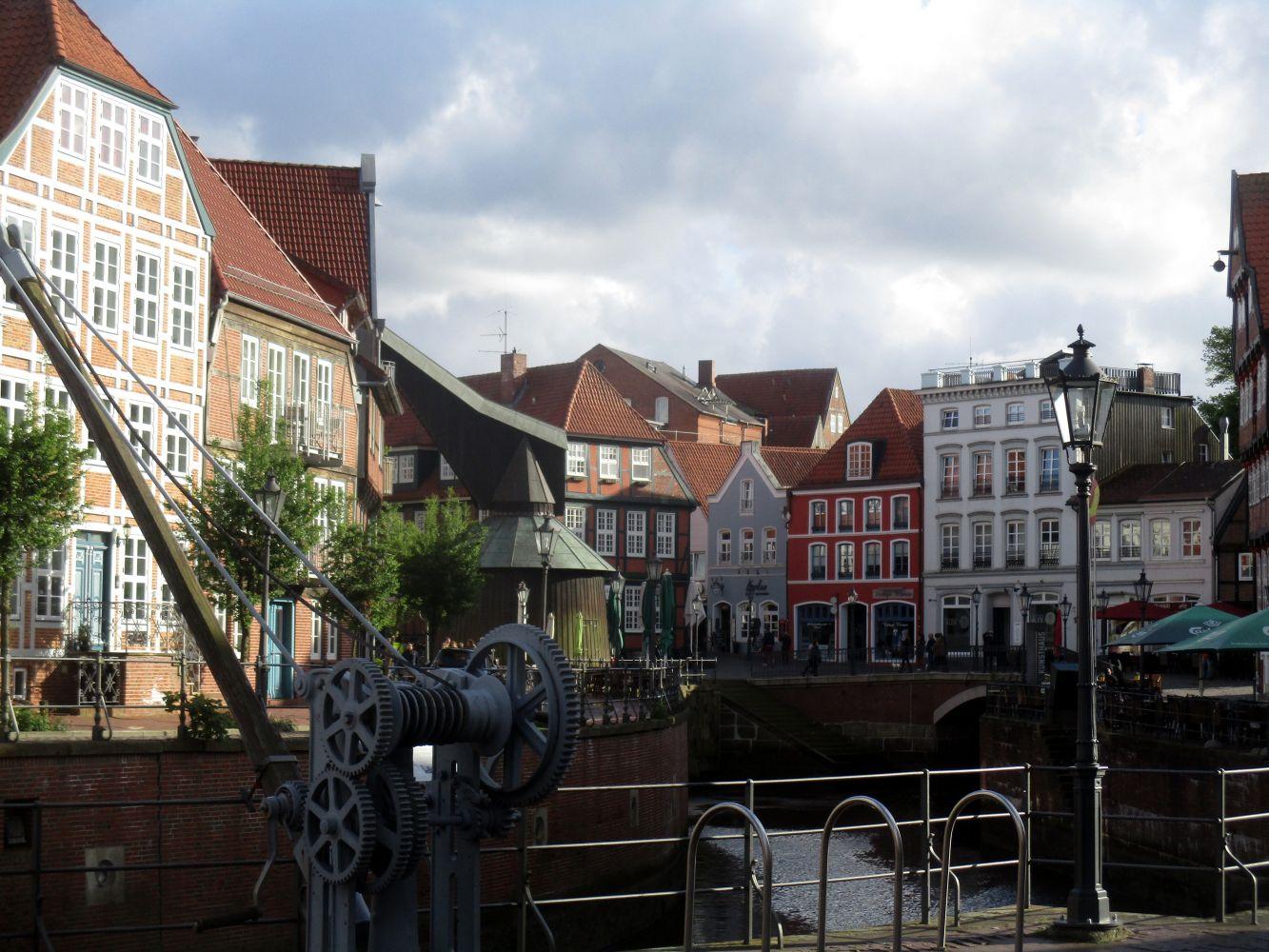 Ein Panorma mit vielen Bunten alte Häusern. Großteils Fachwerk. Ausserdem sind zwei Kräne zu sehen, die im Vordergrund an einem Hafenbecken stehen.
