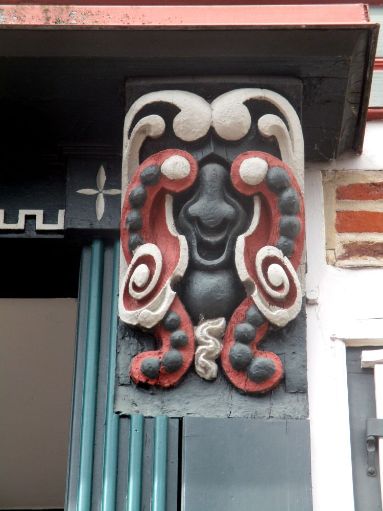 Holzschnitzerei an einem Fachwerkhaus. Die Schnitzerei ist schwarz, weiß und rot bemalt. Sie zeigt ein Gesicht oder eine Maske beim näheren hinsehen. Die Schnitzerei gehört zu einem Haus in der Altstadt von Stade.