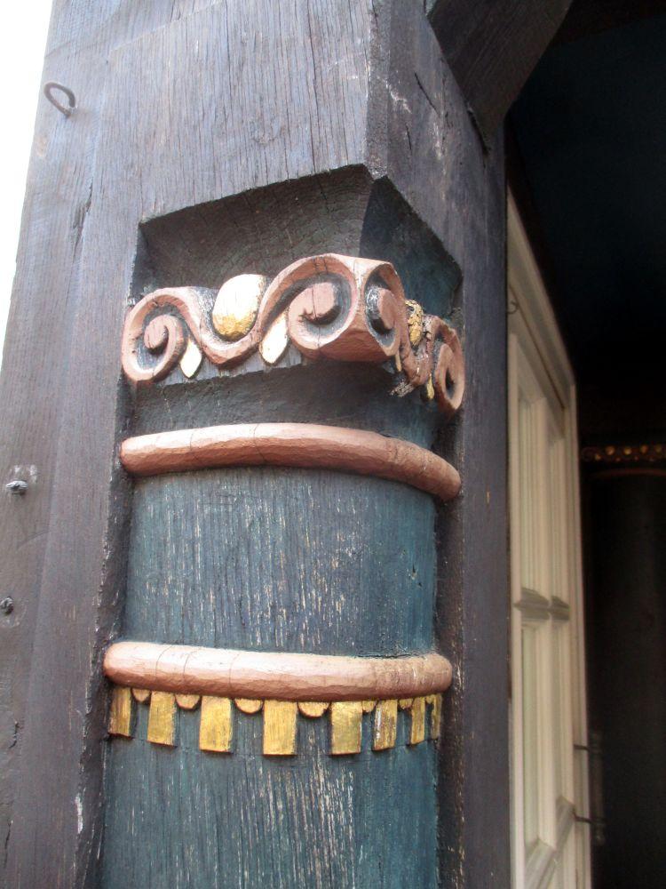 Schnitzerei an einem Fachwerkhaus in Stade. Ein Holzbalken, der so bearbeitet ist, dass er aussieht wie eine Säule, die Grün bemalt ist. Die Säule ist mit Rösanen Zierlienen die umlaufend sind versehen, und het ein Rosa bemaltes Kapitell, das dorisch wirkt. Einge kleinere details sind gold bemalt.
