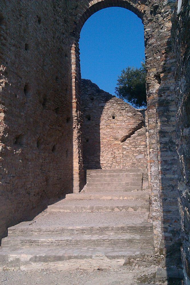 in Trappe in den Grotten des Catull, die durch einen Bogen Führt. Dahinter verläuft eine teils abgebrochene Mauer. Die Gesammte Architektur bestaht aus Hellbraun-rötlichen Ziegeln.