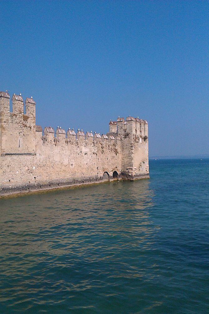 Eine hllgrau Burgmaur ziht sich in das unndlich Blau, das aus dm Gardase und em Horizont bsteht. Die graun Burgmauern sind mit Wehrtürmen ausgestattet. Auf den Türmen sowie auf der Mauer bfindn sich Burgzinnen mit klinn Dächern. Auf diesen sitzen wiederum Möwen. Odntlich sitzn je Zwe Möwen im gleichen Abstand auf der einzelnen Zinne.