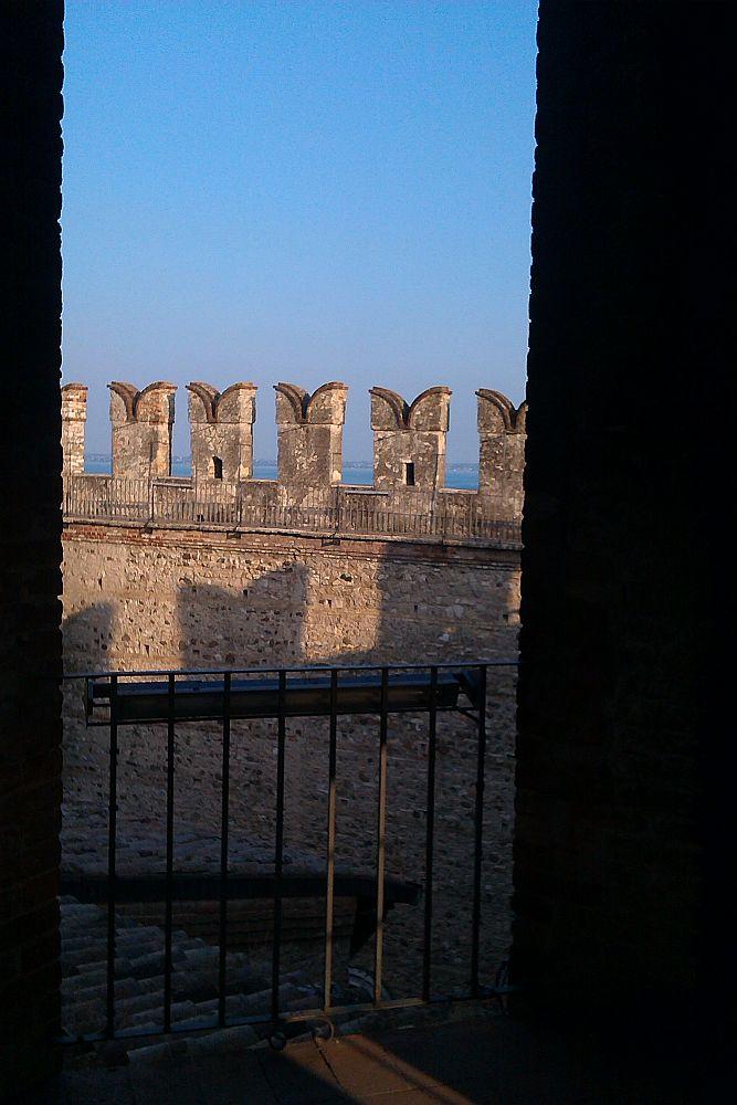 Die Schwalbenschzanzznnen der Wasserburg von Sirmione aus dr Burg heraus fotografiert. Die Abendsonne leuchtet das Mauerwerk vor einem blauen Hintergrund an. Die Zinnen der gegenüberliegenden Seite zeichenen sich als schatten unter der Fotografierten Zinnenreihe ab.