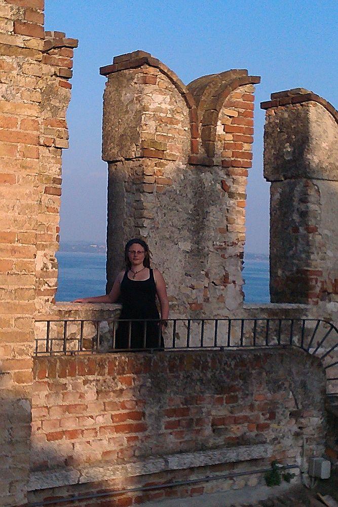 Eine Frau steht nbene einer Schwalbenschwanzzinne der Burg Sirmione. Die Zinne ist gut drei mal so Groß wie die Frau.