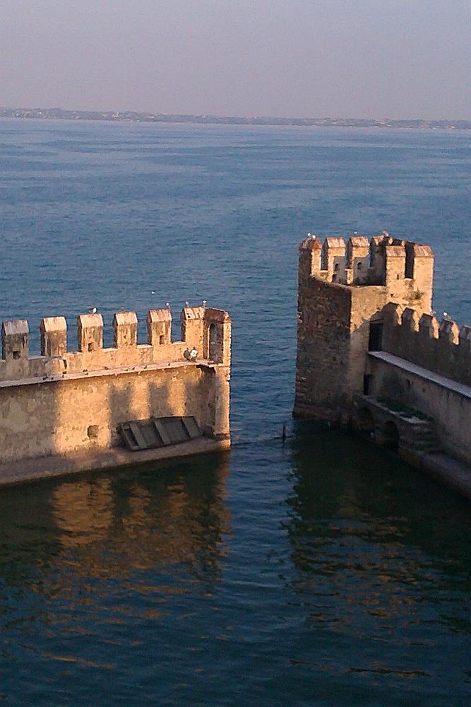 Zwei wehrgänge, geschützt durch Burgmauern mit Zinnen ragen in den endlosen See hienein. Gleichzeitig handelt es sich bei den Bauwerken um die Molen der Hafenanlage der Burg Sirmione