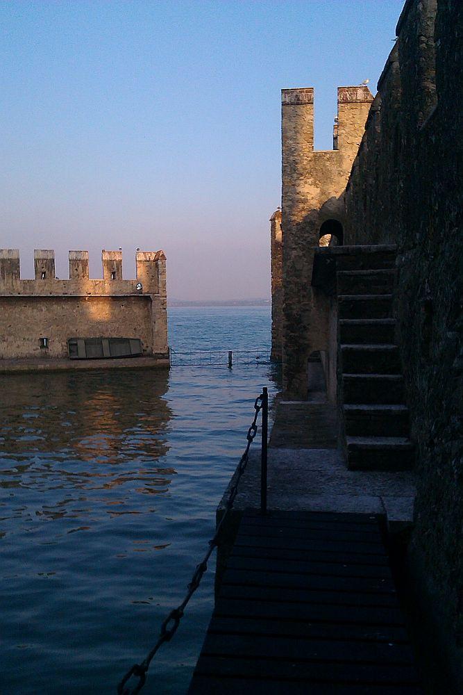Der Ausgang des Hafens. Es handelt sich um zwei Wehrgänge, die kurz über der Wassroberfläche einen Gehweg aufweien, und in einer art Tor, einen aus Wehrgängen mit Zinnen Geschützten Hafenmolen bestehen.