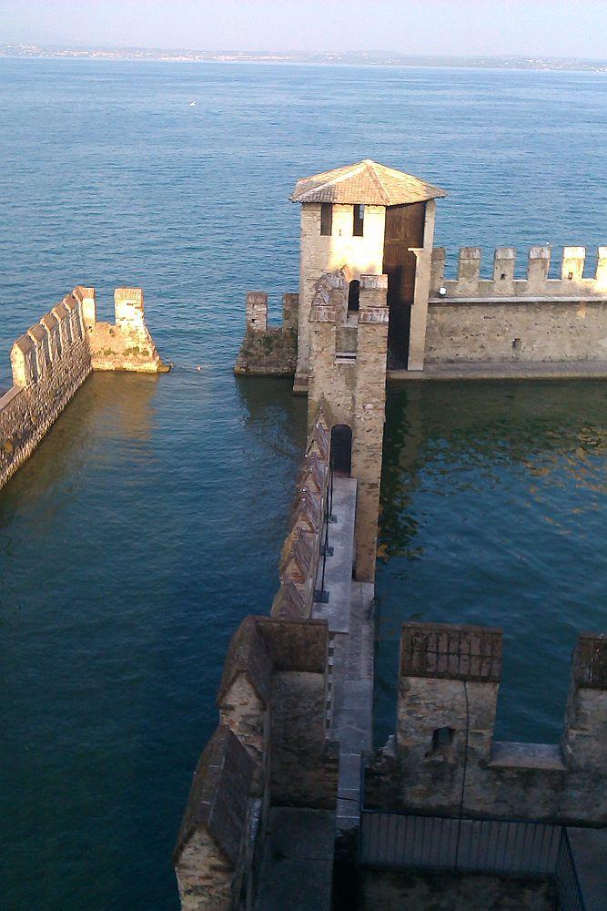 Ein Teil des Burghafen aus der Vogelperspektive. Eine Mauer unterteilt zwei bereich des Hafens. Einn Inneren vin Mauern umschlossenen Teil, und einen äusseren, über das Wasser mit einem Boot zugänglichen Teil.
