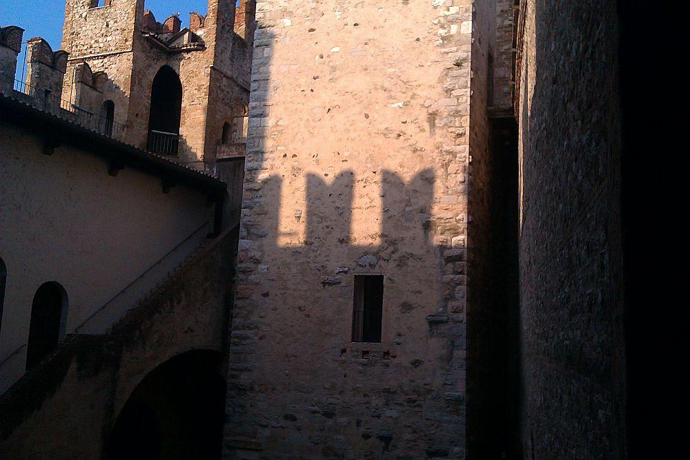 Die Abendsonne scheint in dn Burginnenhof. Auf den Wändn der Burg zeichent sich dadurch ein Schattenspiel an den Wänden ab.