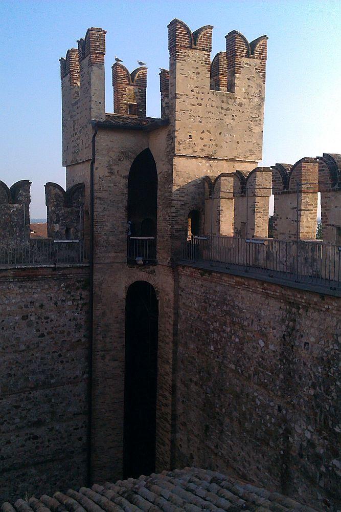 Der Wehrgang auf der Innnseite der Burg Sirmione. Nach innen hin ist dr Gang mit einem modrnen Gitter gesichert. Im Mittelalter handlte es sich alo um einen Weg endlang dr durch Zinn geschützten aussenmauer, der nach innn hin allerdings keine weitere Sicherung hatte.