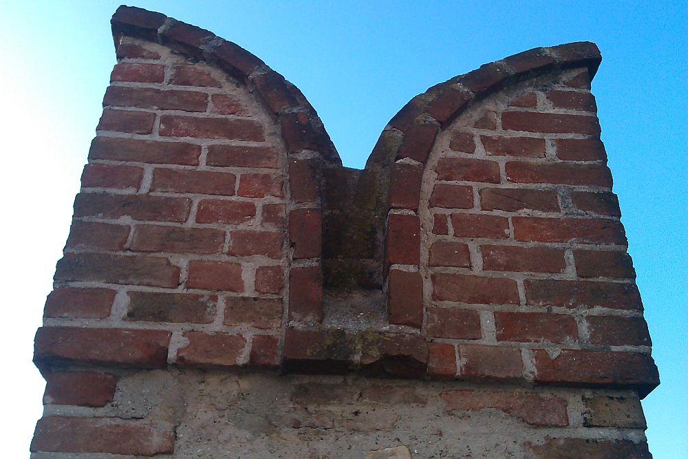 Eine Schwalbenschwanzzinne in Nahaufnahme. Die Burgzinne ist aus Roten Ziegeln Gemuert. Der obere Abschluss bestaht aus zwei halbrunden nach aussen gekehrt Mauerwerken. Diese sind abgedeckt mit einer schicht halbrund verlaufender Ziegel.