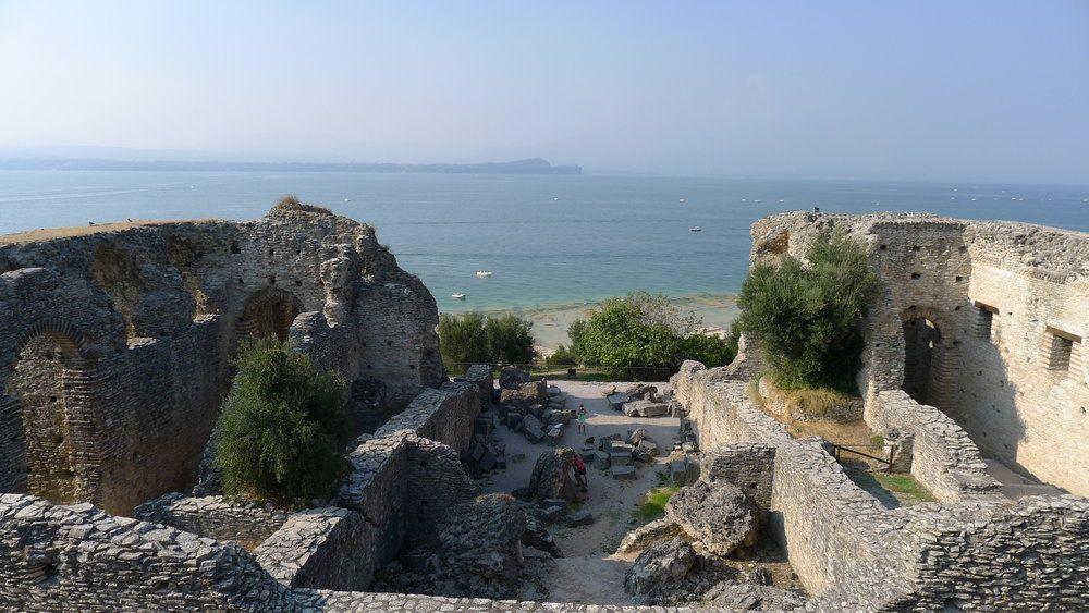Ausblick auf inen Archäologischen Befund von Oben. Es handelt sich um die Ruine eines Großen Gebäudes. Auf der Rückwärtiegen seite Fehlt eine Wand, dadurch wird das Blaue Wasser des Gardases dierkt sichtbar.