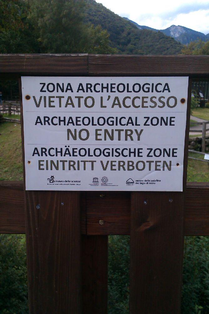 """Ein Schild in drei Sprachen. Es ist beschriftet mit """"Archäologische Zone - Eintritt Verboten"""". Das Schild ist an einem Holzzaun befestiegt. Es Stammt aus dem Pfahlbaumuseum am Ledrosee in Norditalien."""