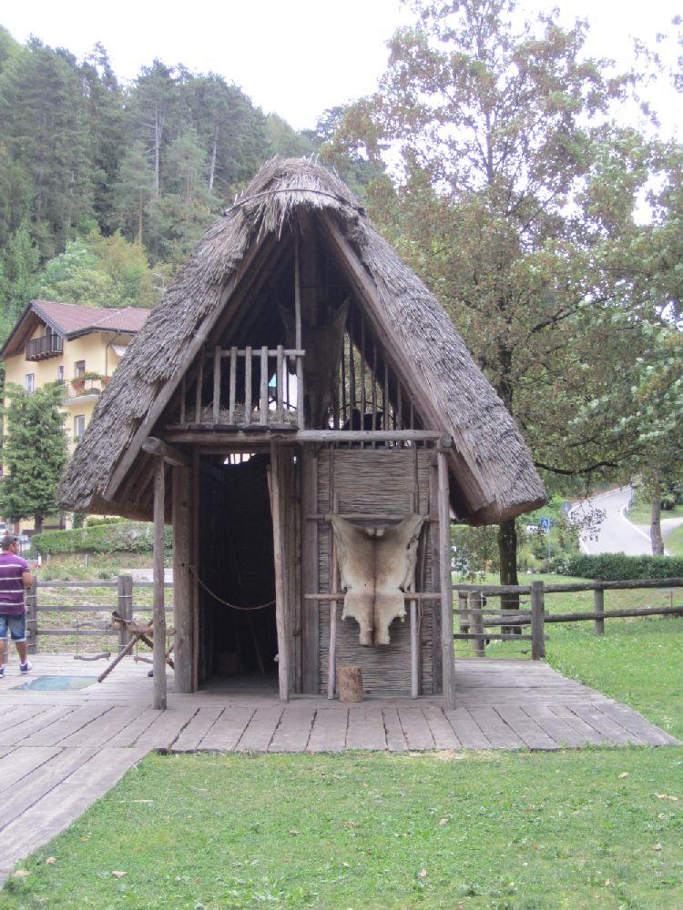 Ein Holzhaus mit aus Ästen geflochtenen Wänden. Das Gebäude ist klein, und hat ein Geschoss und ein Dachgeschoss. Es ist von der Giebelwand her zu sehen. Vor dem Gebäude steht ein Fell aufgestellt.